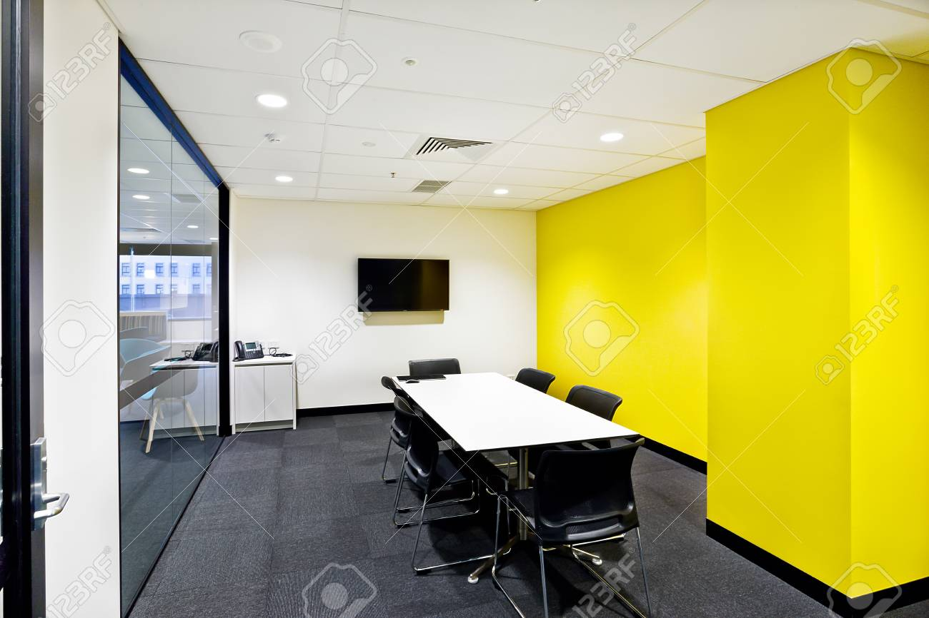 Small Meeting Room With Yellow Walls And Tv Next To Glass Stock ...