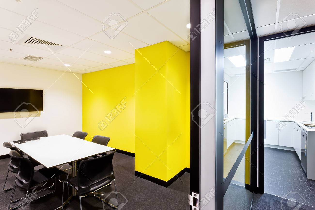 Small Conference Room With Yellow Walls And Hallway To The Kitchen ...