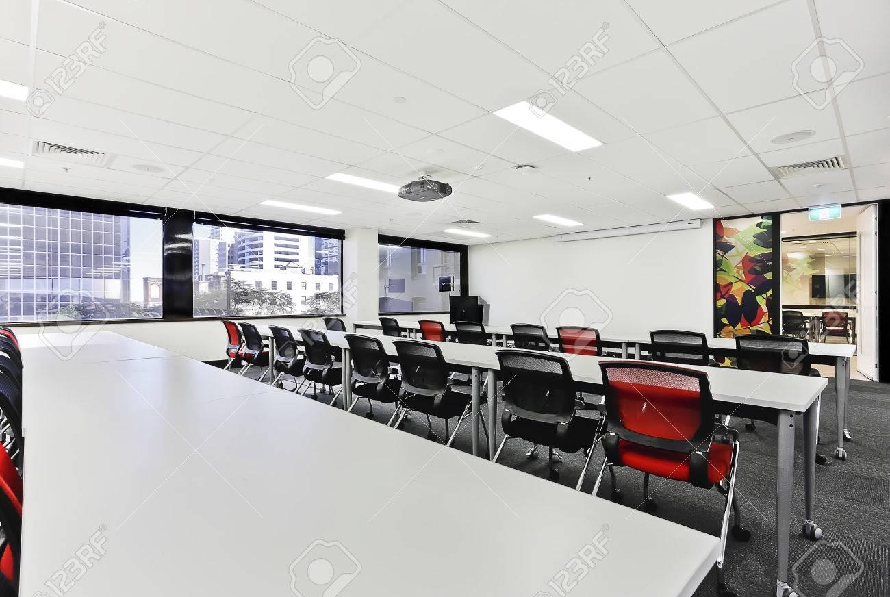 sala de reuniones moderna con largas mesas y sillas cubiertas con paredes blancas foto de archivo