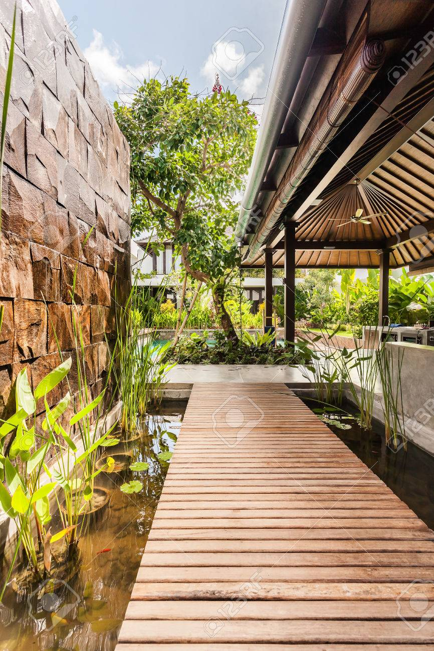 Stock Photo   Wooden Path Over Water Pond In A Modern Hotel Under  Traditional Roof Near To The Wall
