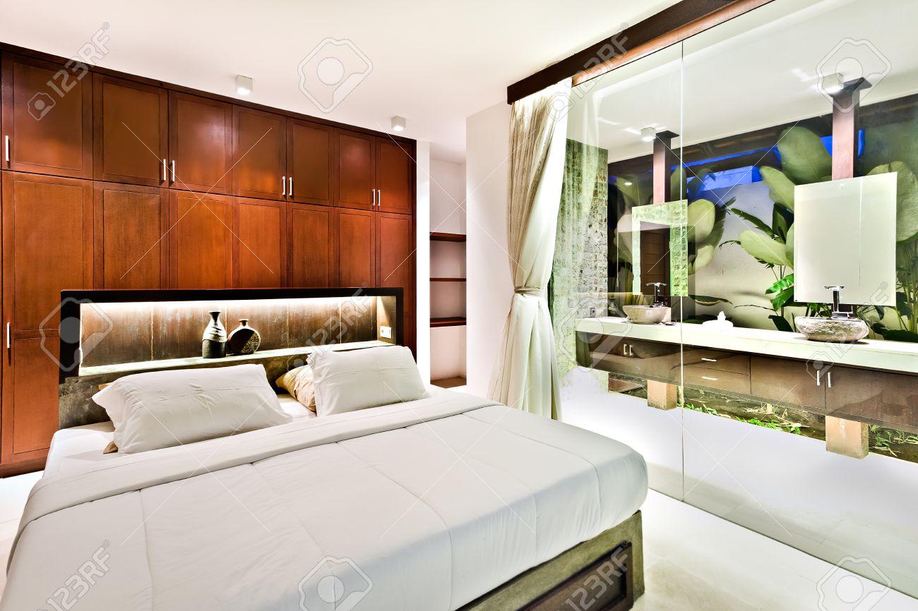 dormitorio moderno en una casa de lujo con muebles de madera y pared de cristal al