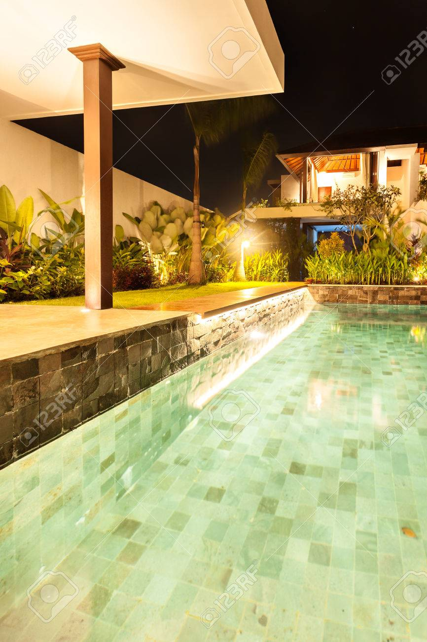 Closeup of an illuminated swimming pool with lights which belongs to fancy house or hotel at