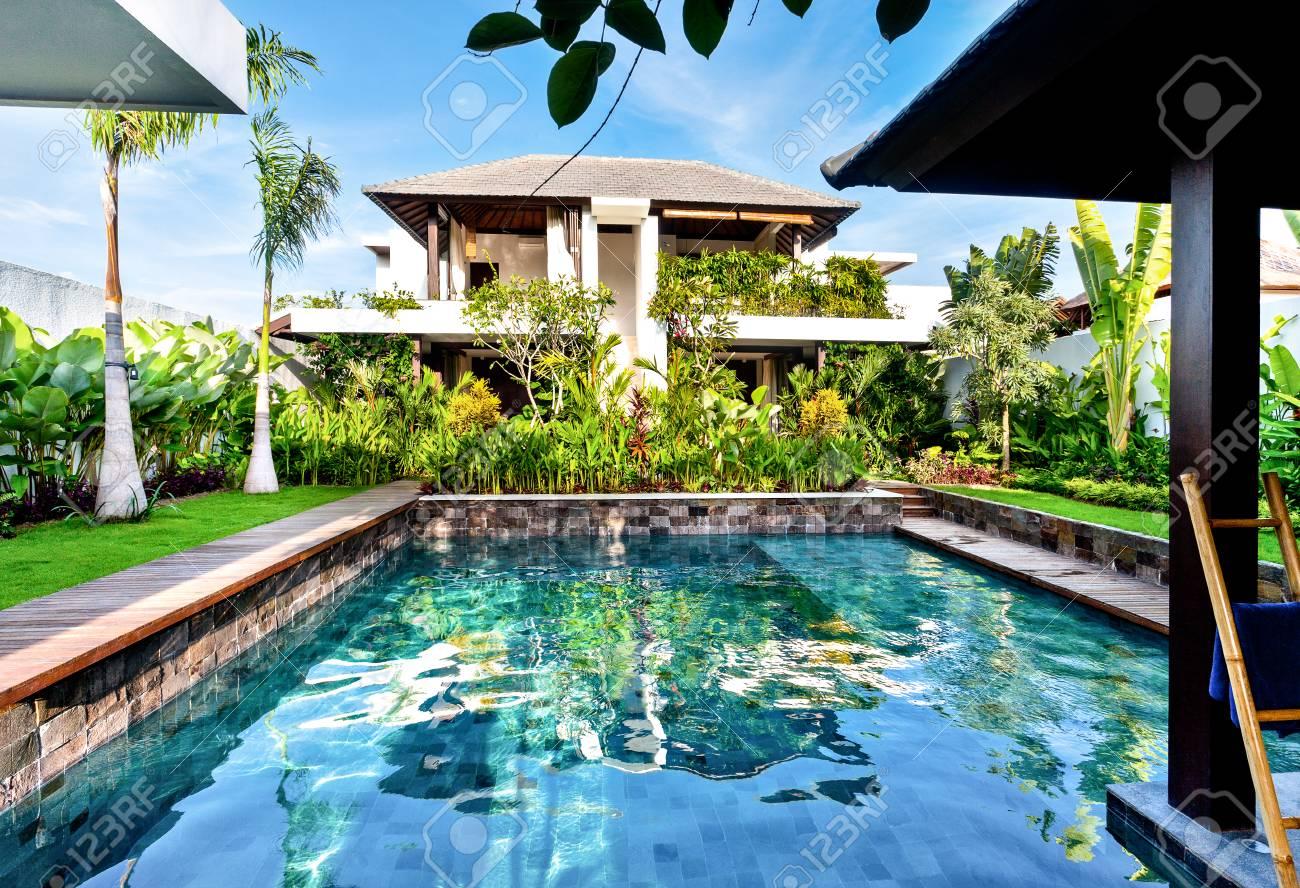 Piscine de luxe qui brille avec la lumière du soleil dans une maison  moderne avec un jardin verdoyant sous le ciel bleu