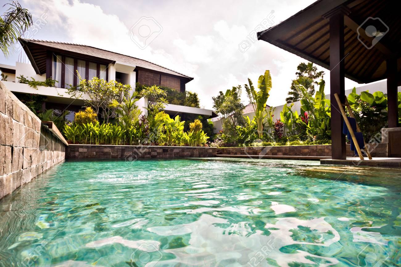 Giardino Di Una Casa piscina tradizionale con muri in pietra è coperto di alberi e piante nel  giardino di una casa nel tempo di mattina