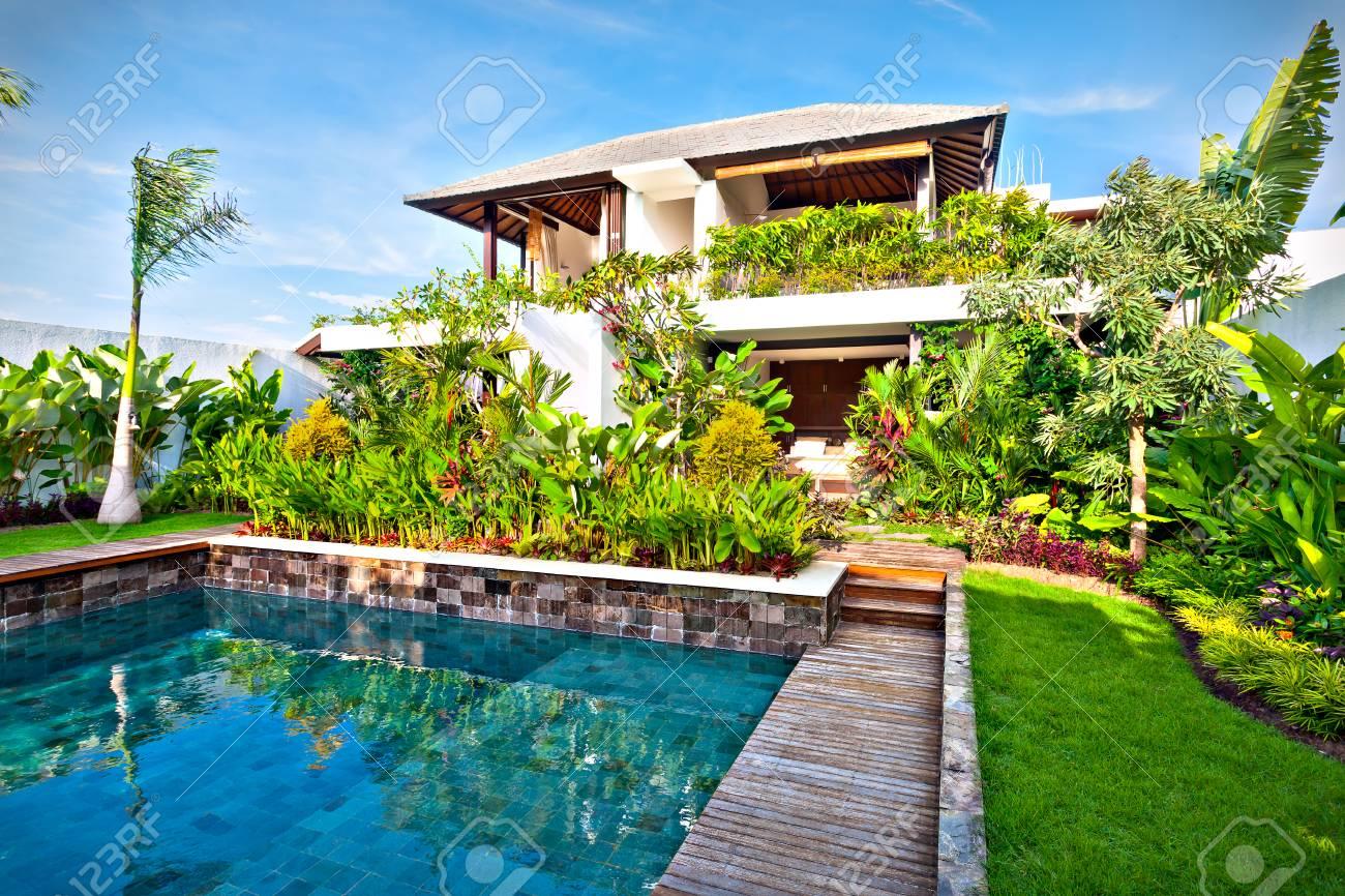 Conception de décoration de jardin de fantaisie d\'une maison moderne, y  compris une piscine d\'eau bleue avec pelouse et un jardin rempli de plantes