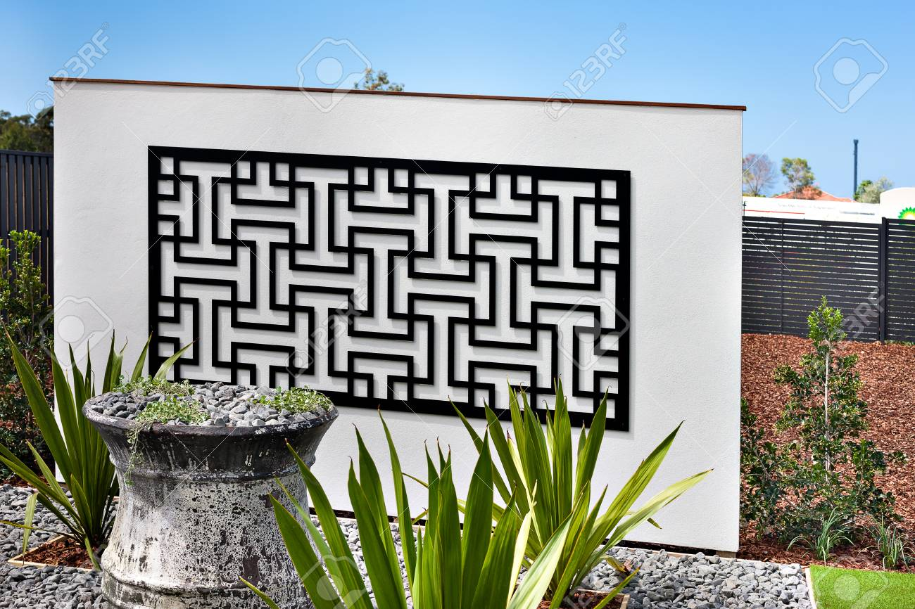 Gros plan d\'un jardin avec couleur gris gravier vase fabriqués dans des  usines de béton et de fantaisie autour de lui, près du mur et la clôture  avec ...