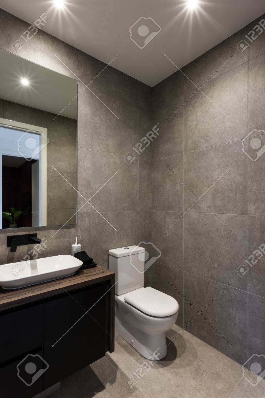 Modern Bathroom Including Black Color Faucet And Sink With A Mirror Next To  The Toilet Bowl