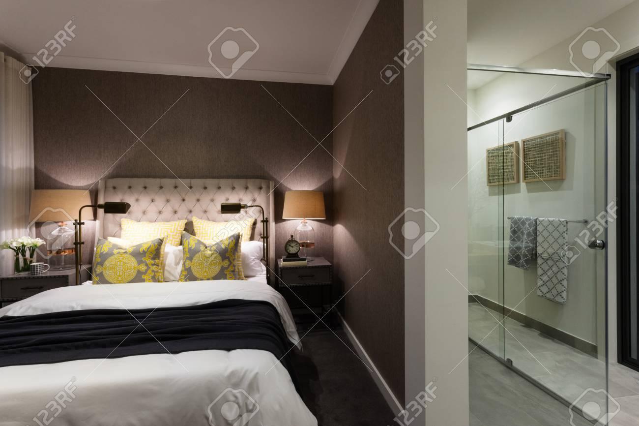 Camera da letto moderna di una casa o hotel attaccata ad un bagno con  doccia con copertura in vetro e asciugamani
