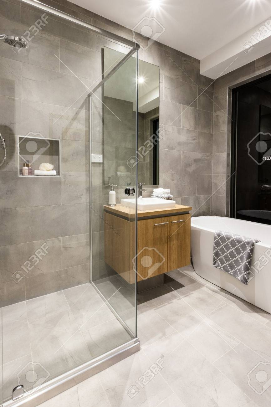 Salle de bain moderne avec coin douche recouvert de verre à côté d\'un  placard en bois et robinet à côté d\'une baignoire blanche
