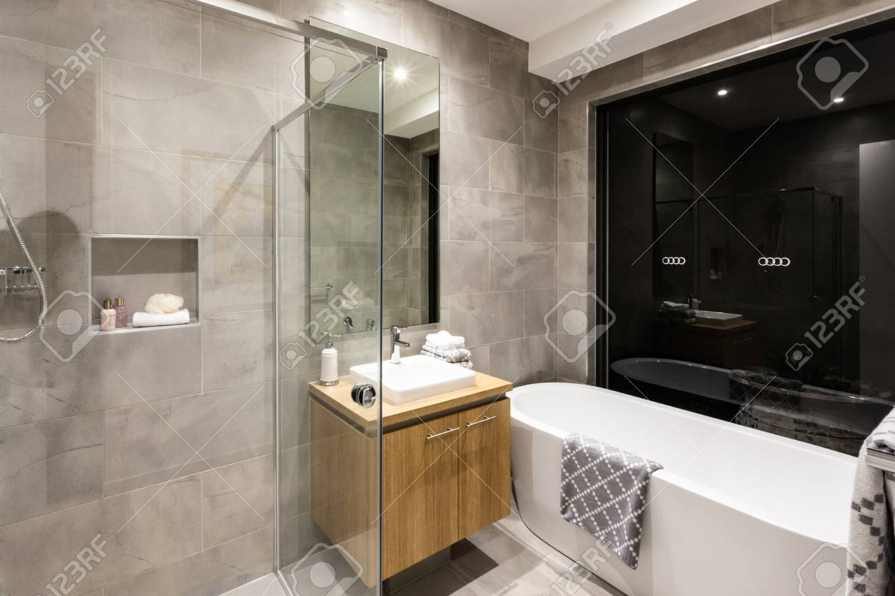Modern Bathroom With A Shower And Bathtub Next To A Mirror And ...