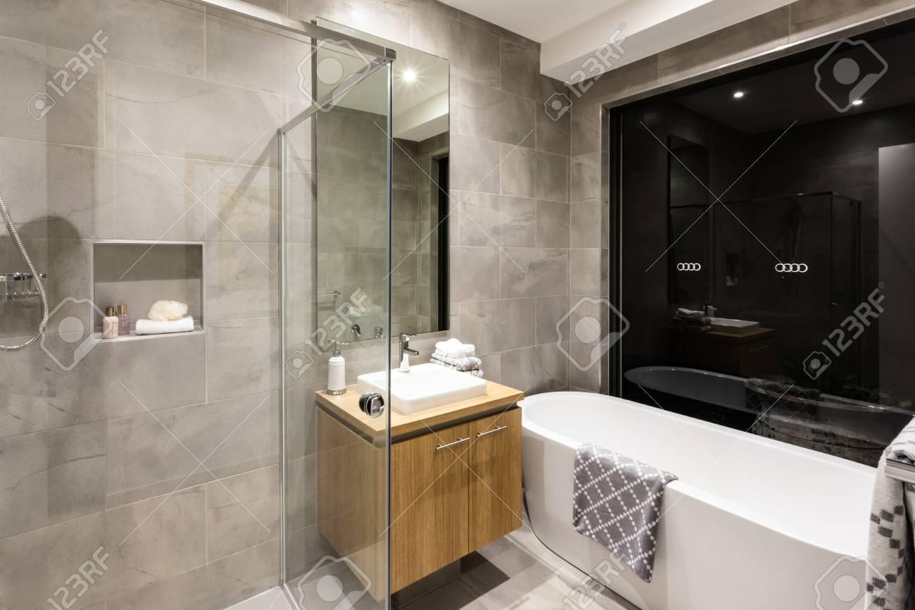 Salle de bain moderne avec douche et baignoire à côté d\'un miroir et  robinet avec lavabo éclairé la nuit