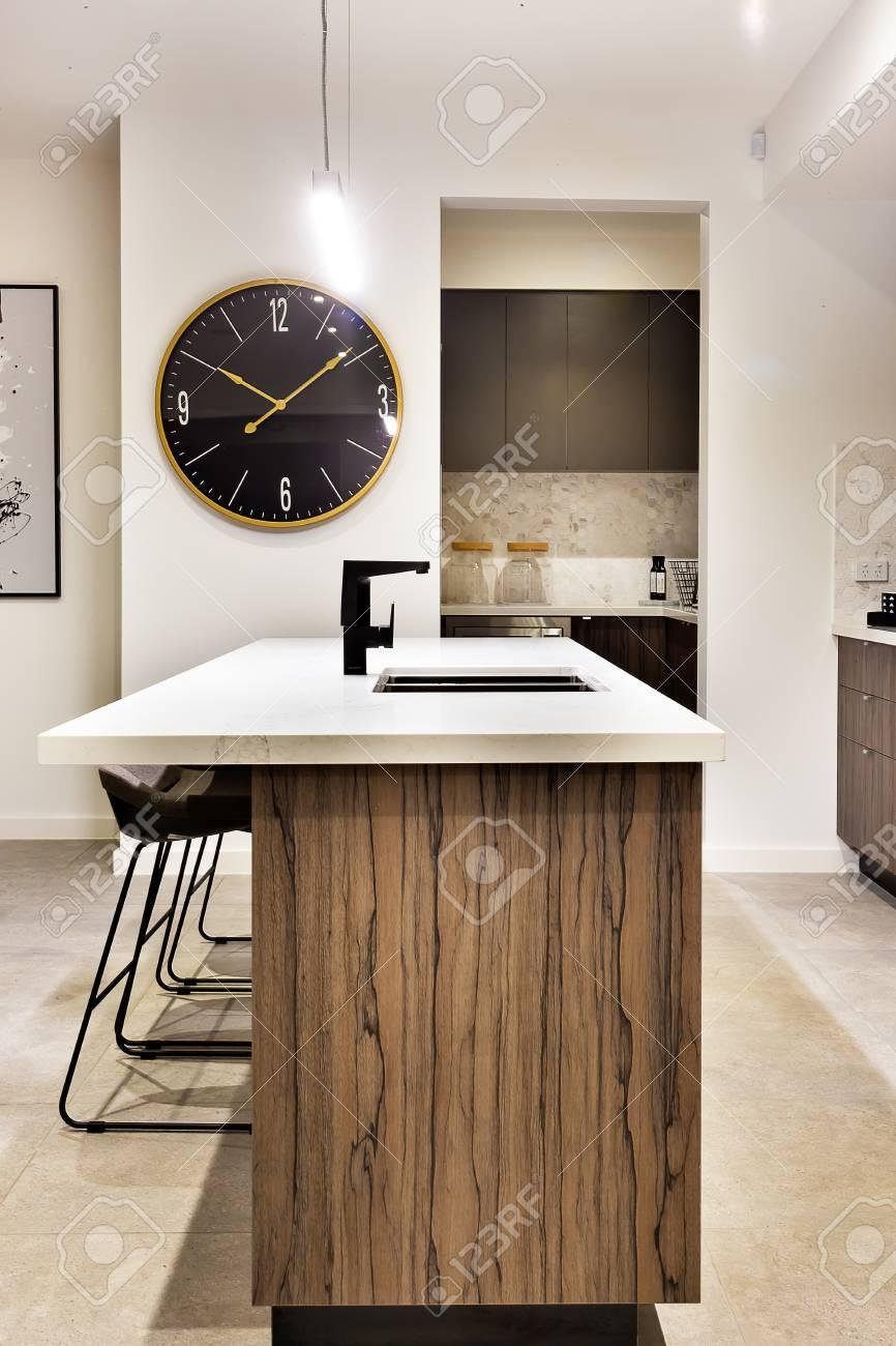 moderne küchenarbeitsplatte aus holz mit einer wand uhr und stühle