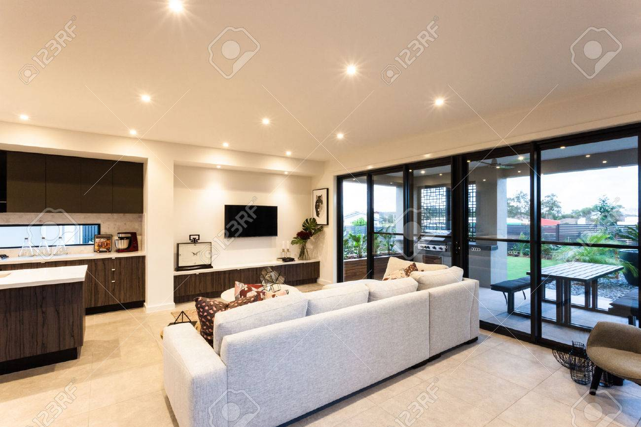 Luxurious Living Room With Sofas, Televisions And Kitchen Beside Entrance  To The Outside Patio Area