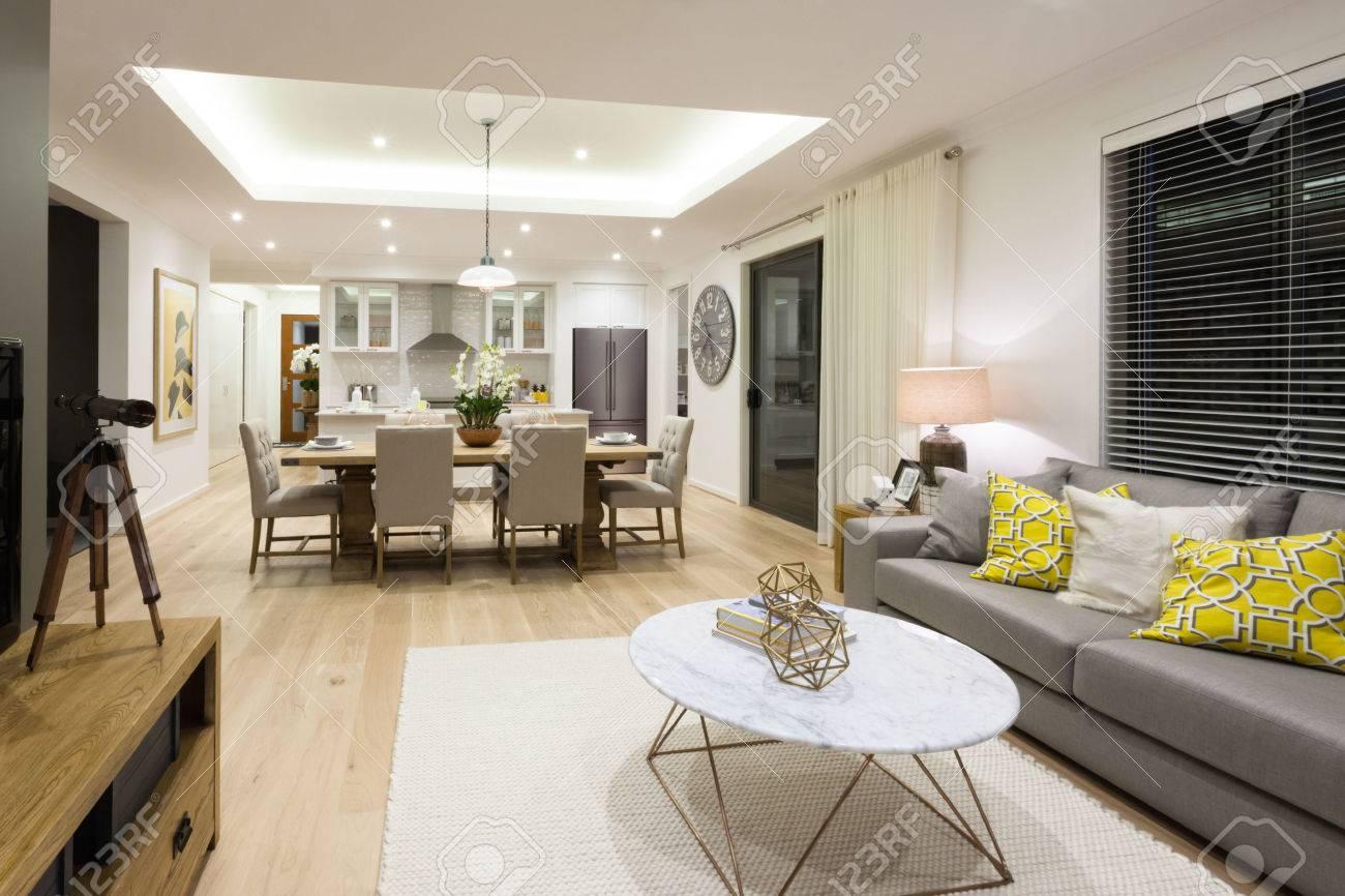 Moderna sala de estar que incluye sofás, sillas y mesas al lado de la  cocina y el comedor iluminado el uso de luces en la noche