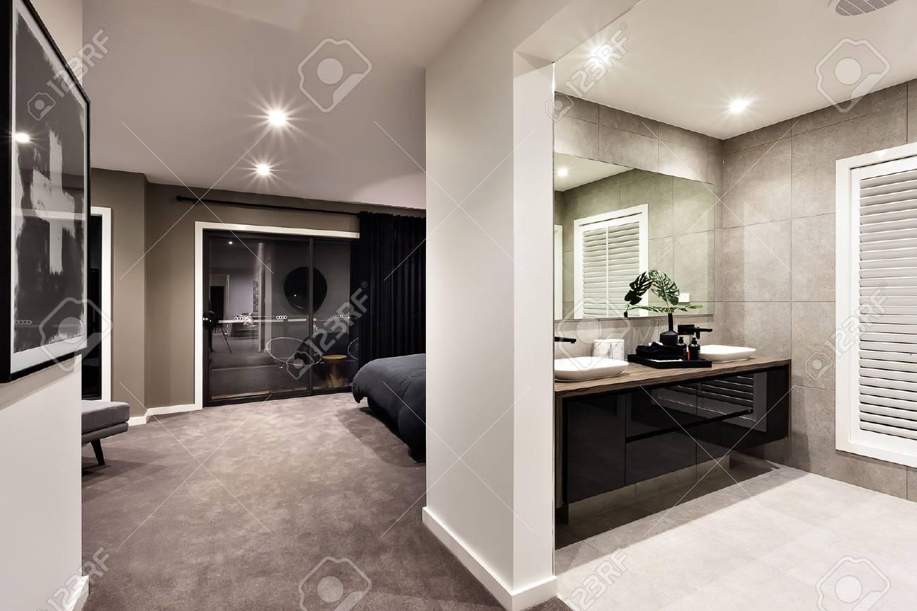 Toilettes modernes et couloir vers une autre pièce à travers la porte en  verre noir