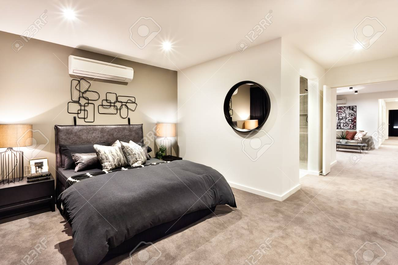 Modern bedroom with a hallway to other rooms and illuminated..