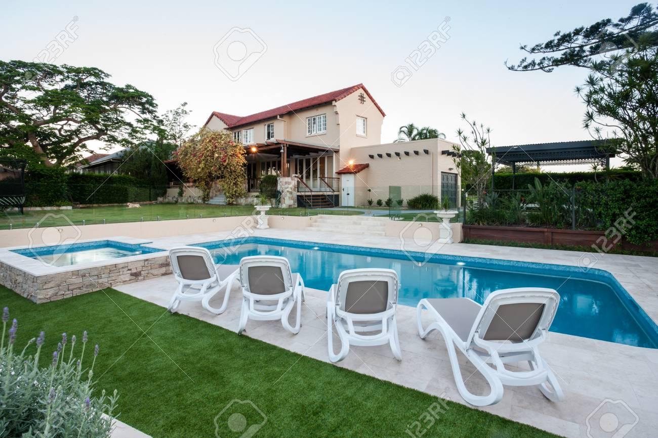 Piscina Moderna En Frente De La Casa Con Un Césped Verde Con Jardín Alrededor Hay Sillas En El Lado De La Piscina Cerca A La Pequeña Fuente De Agua