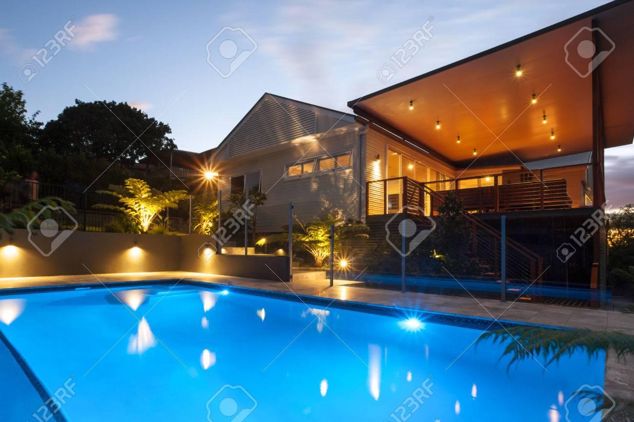 hôtel avec feux clignotants autour de la piscine la nuit avec la lumière du  ciel, il y a des zones sombres autour de la maison avec jardin des