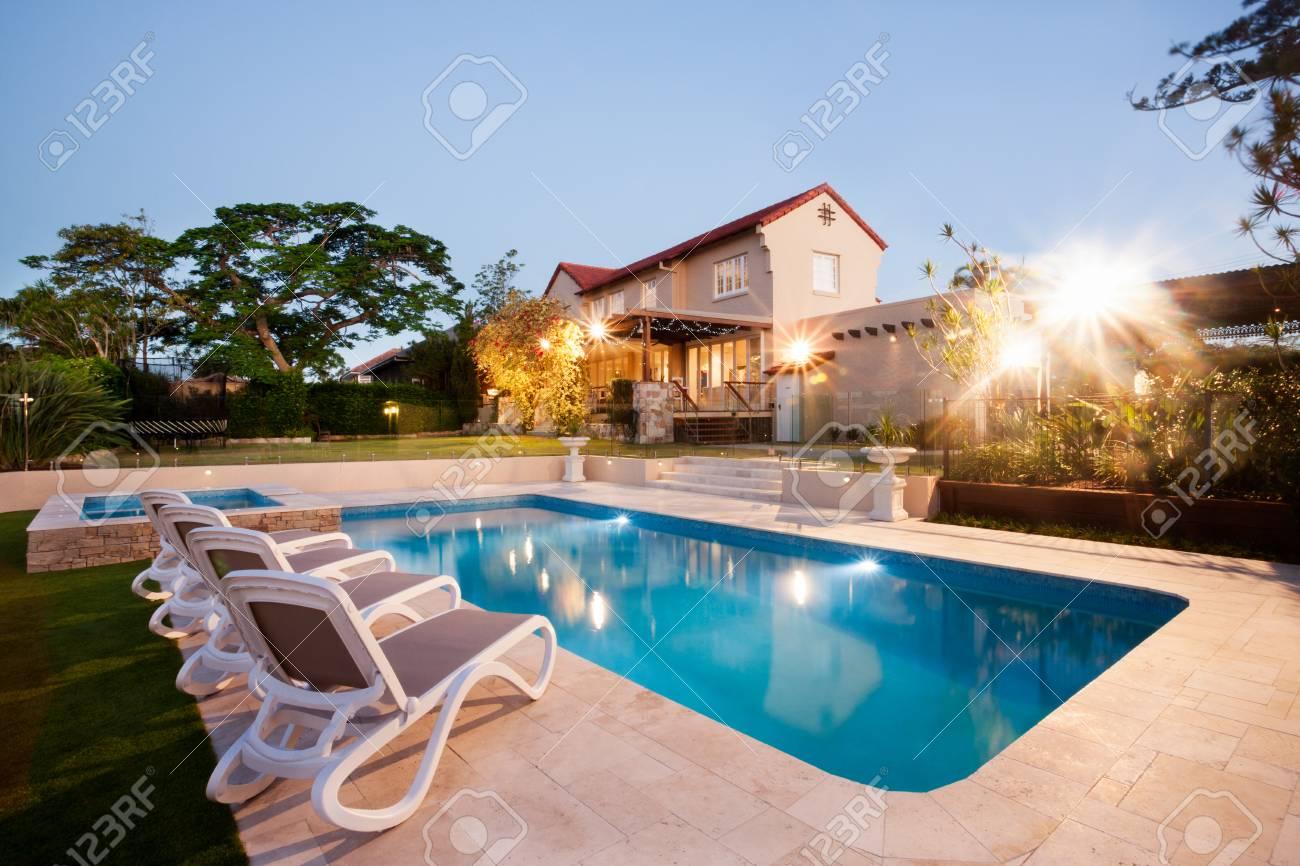 maison de luxe et piscine décoration à une soirée avec des lumières  clignotantes autour du jardin avec des arbres, il y a une pelouse verte  autour