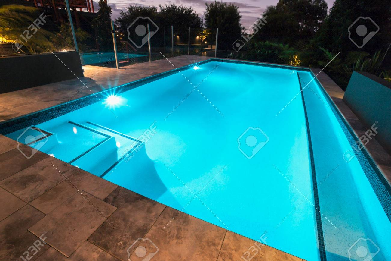 Blue water swimming pool with flashing lights with floor tiles blue water swimming pool with flashing lights with floor tiles surrounded by dark trees in a dailygadgetfo Choice Image