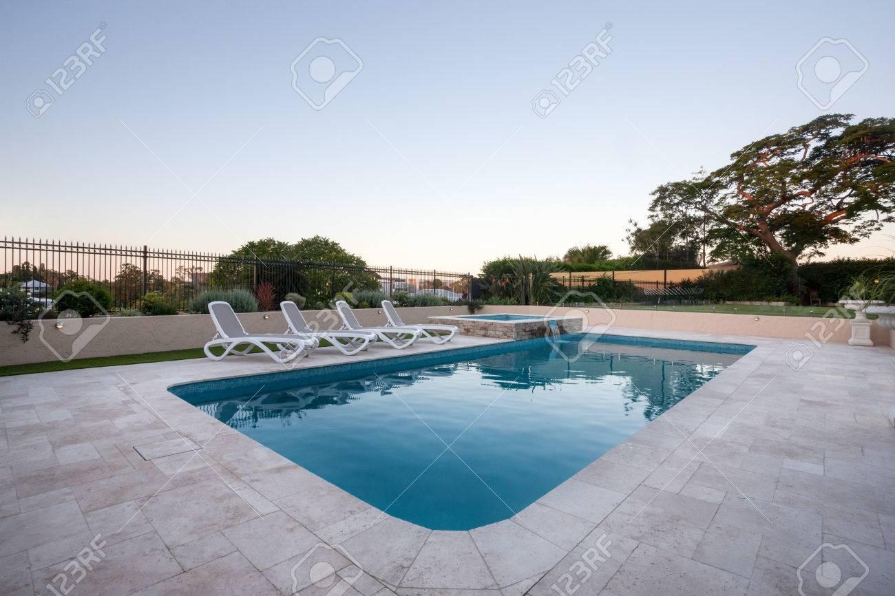 piscine d'eau bleue d'une maison moderne ou à l'hôtel avec un jardin avec  des arbres et clôture autour, le sol est en carreaux de couleur gris.