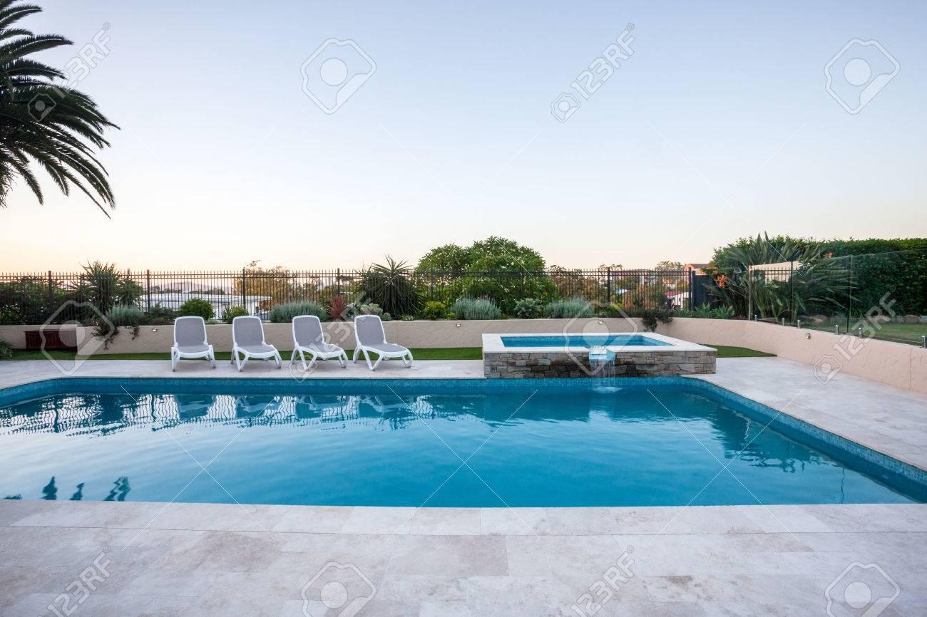 piscine de luxe avec une petite fontaine couverte avec une clôture à côté  des arbres du jardin sous le ciel bleu, il y a des chaises autour de la