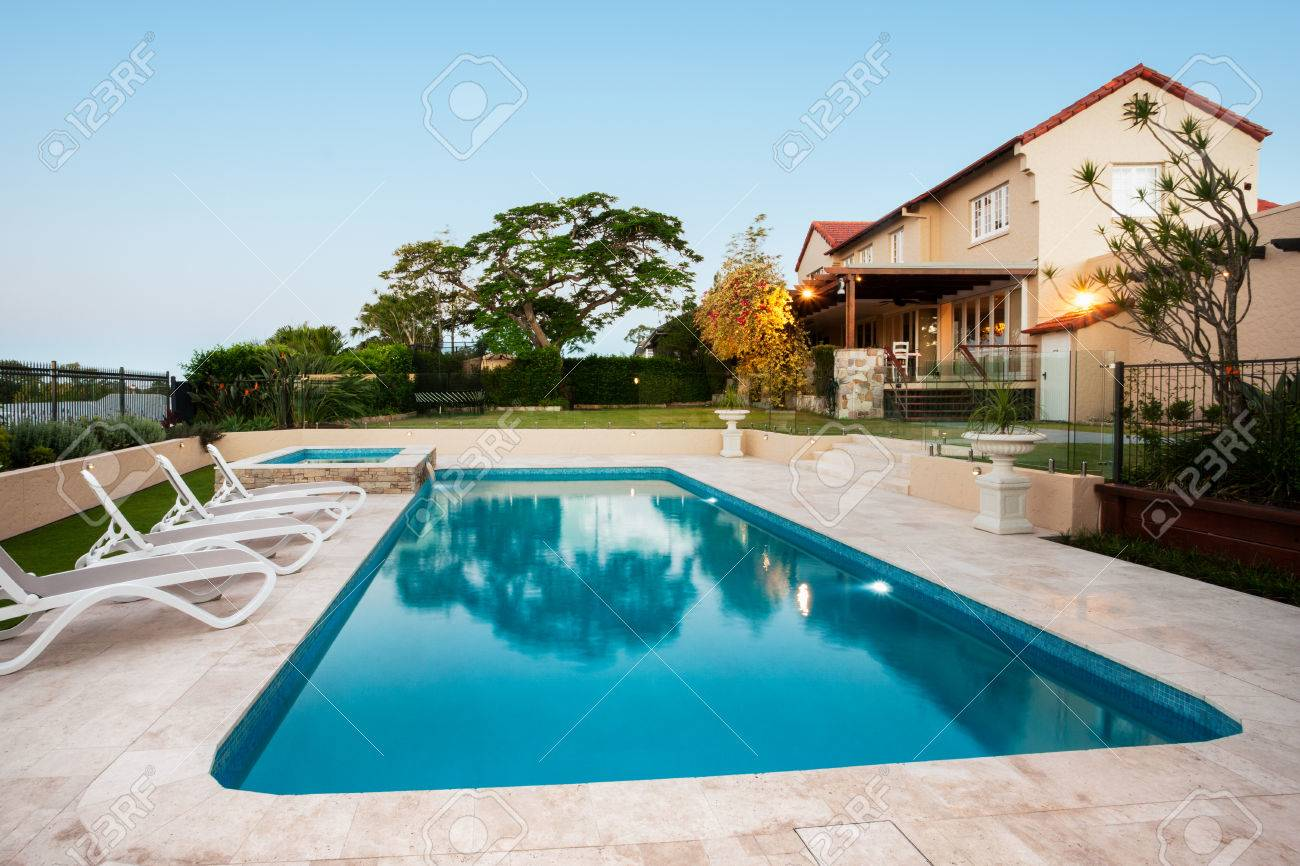 Light Blue Water Swimming Pool Of A Luxurious Mansion With Chairs Around  It. There Are