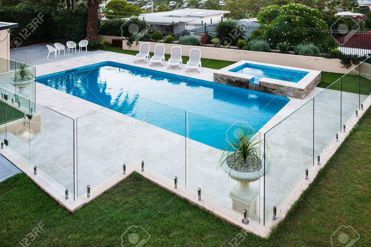Modern swimming pool covered with glass panels beside a green..