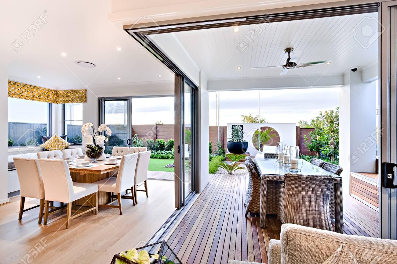 Salle à manger moderne attenante au patio extérieur avec un jardin  comprenant une pelouse verte et un vase, la table à manger installée sur le  parquet ...