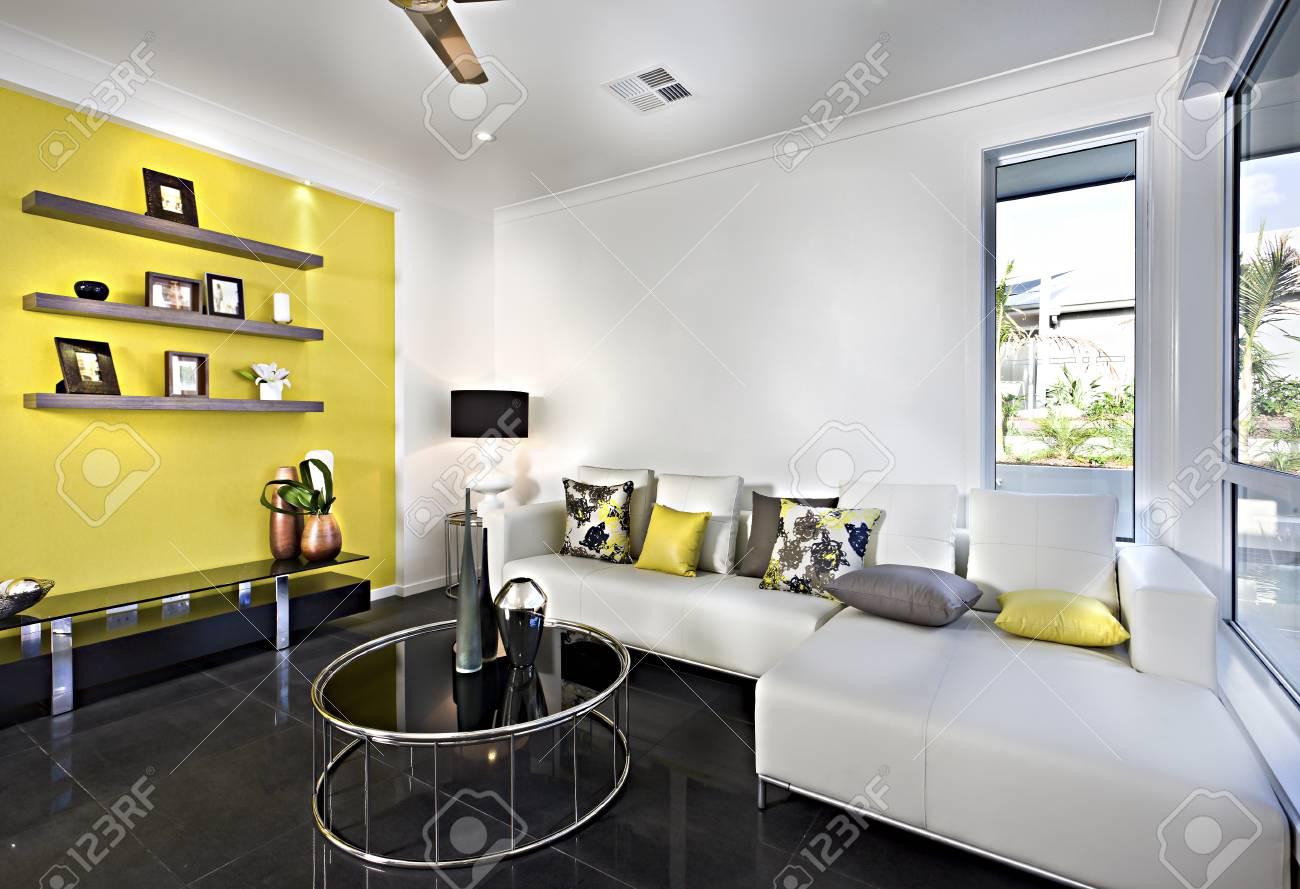 Salon classique avec un canapé et des oreillers avec un sol en carrelage  réfléchissant et une table ronde, il y a un support sur le mur jaune et ...