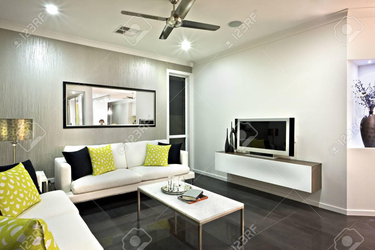 Wohnzimmer mit einem Spiegel und Fernseher unter dem Ventilator an der  Decke schließen, gibt es ein Sofa mit Kissen in der Nähe der kleinen Tisch  auf