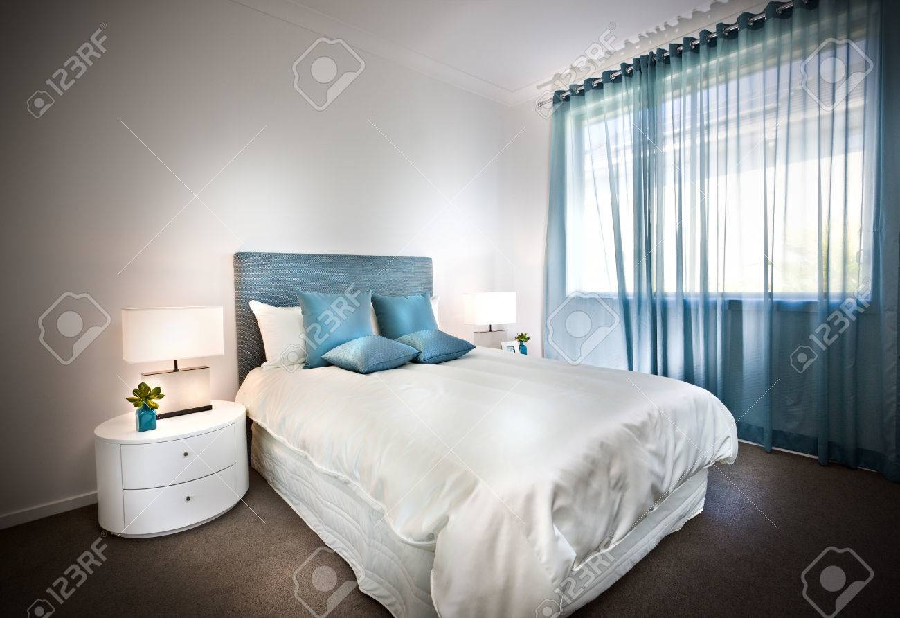Modern Bed With White Sheets And Blue Pillows With Table Lamps Illumination  On The Small And
