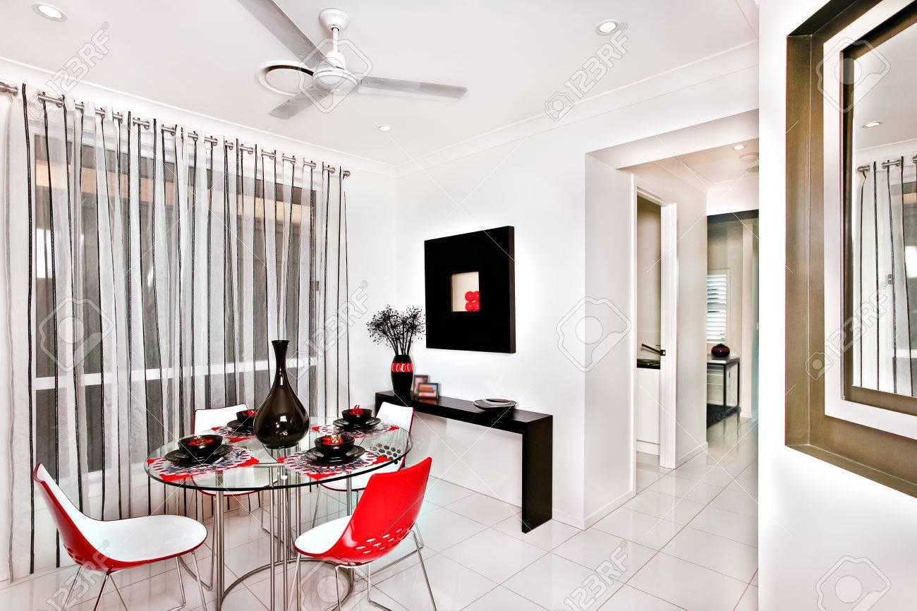 Salle à manger intérieure colorée et classique d\'une maison moderne avec  des carreaux de sol, il y a une table ronde en verre tenant un vase noir ...