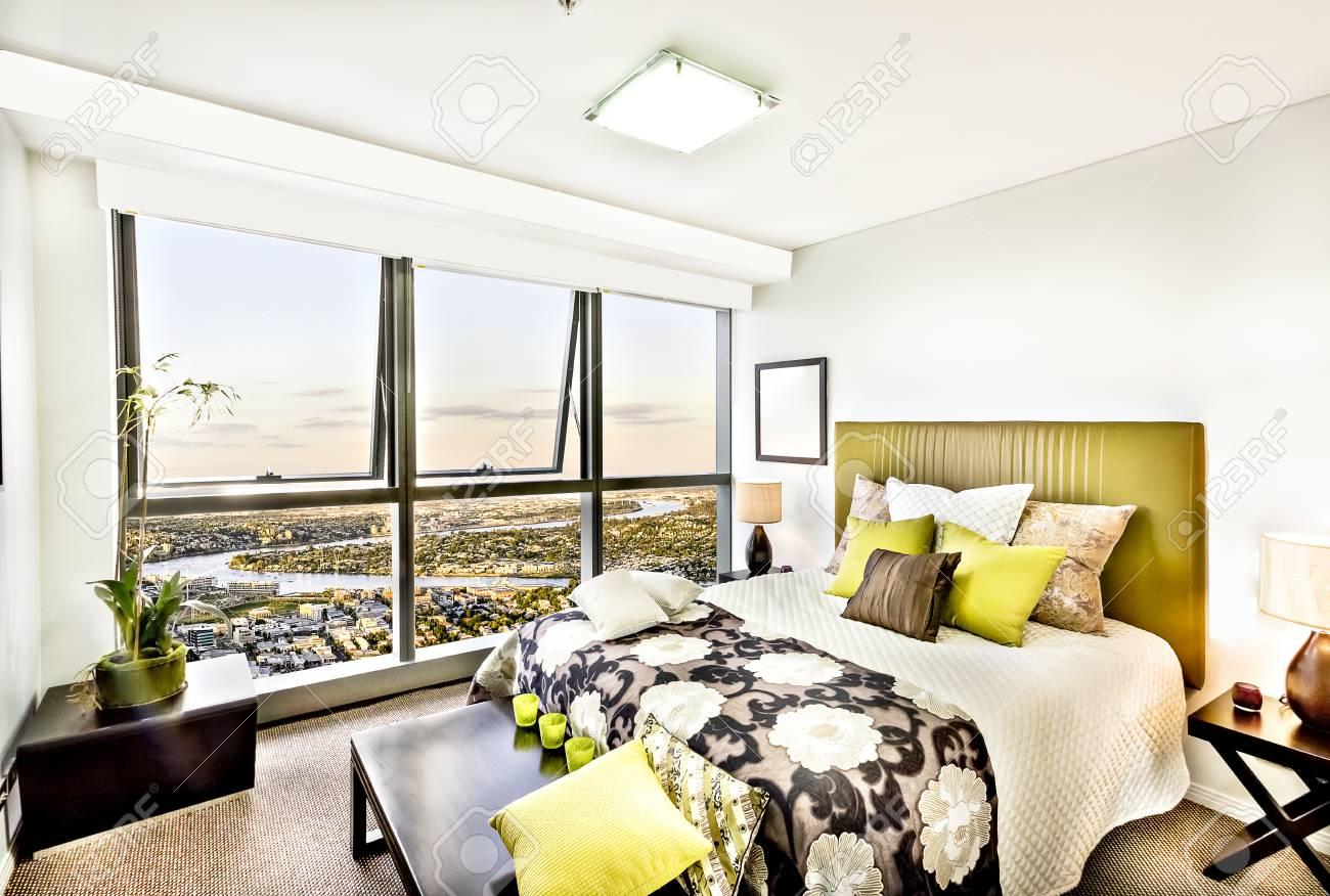 Camera da letto moderna e colorata con vista sulla città, lussuosa area con  finestre e lampade attraenti vicino al pannello di vetro, cuscini sul ...