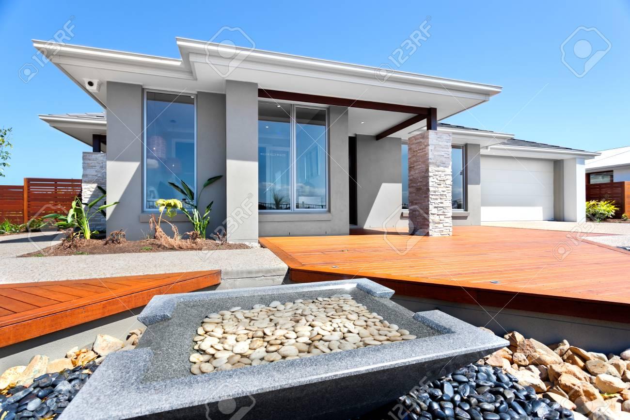 Cour et jardin bien décoré avec des éléments de pierre en face d\'une maison  moderne, gros plan d\'un petit étang de forme carrée faite par pierre pur ...