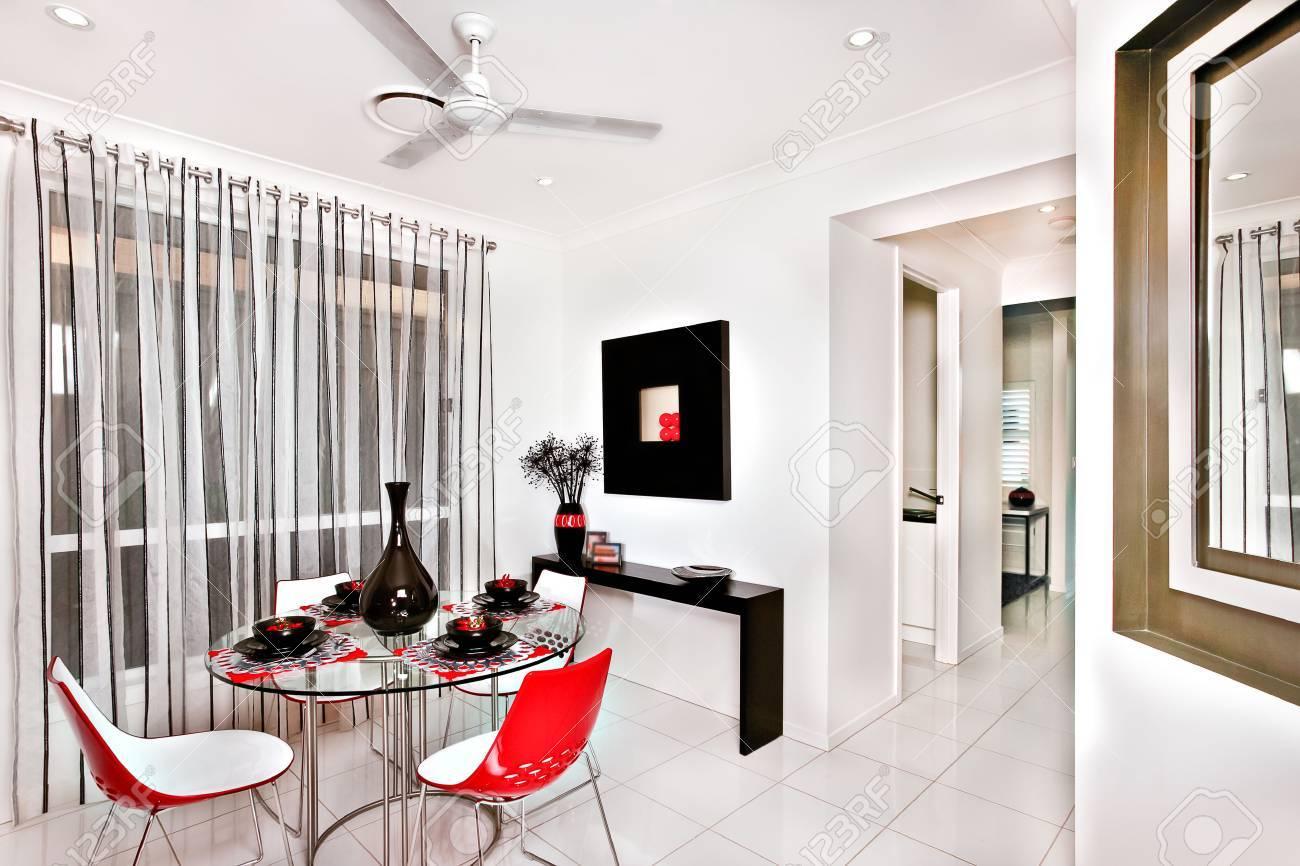 Interior colorido y clásico comedor de una casa moderna con baldosas, hay  una mesa redonda de cristal que sostiene un vaso negro brillante rodeado de  ...