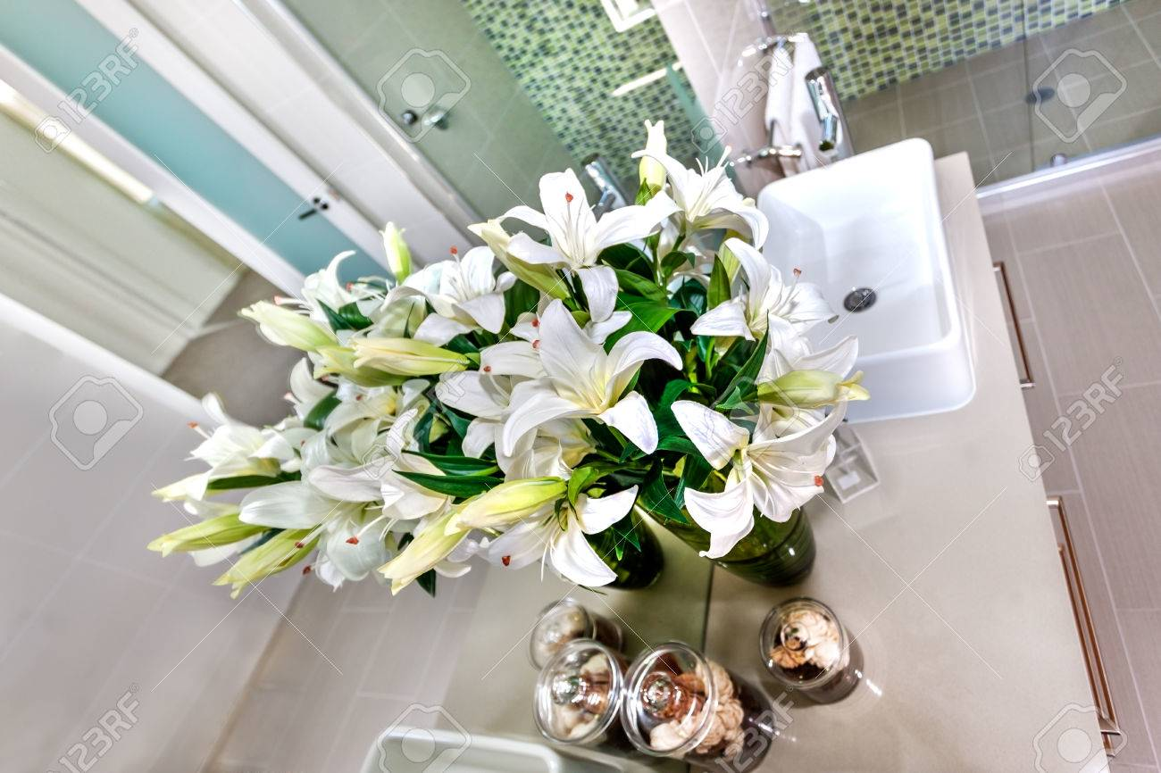 White Flowers And A Modern Washstand With A Green Color Shiny