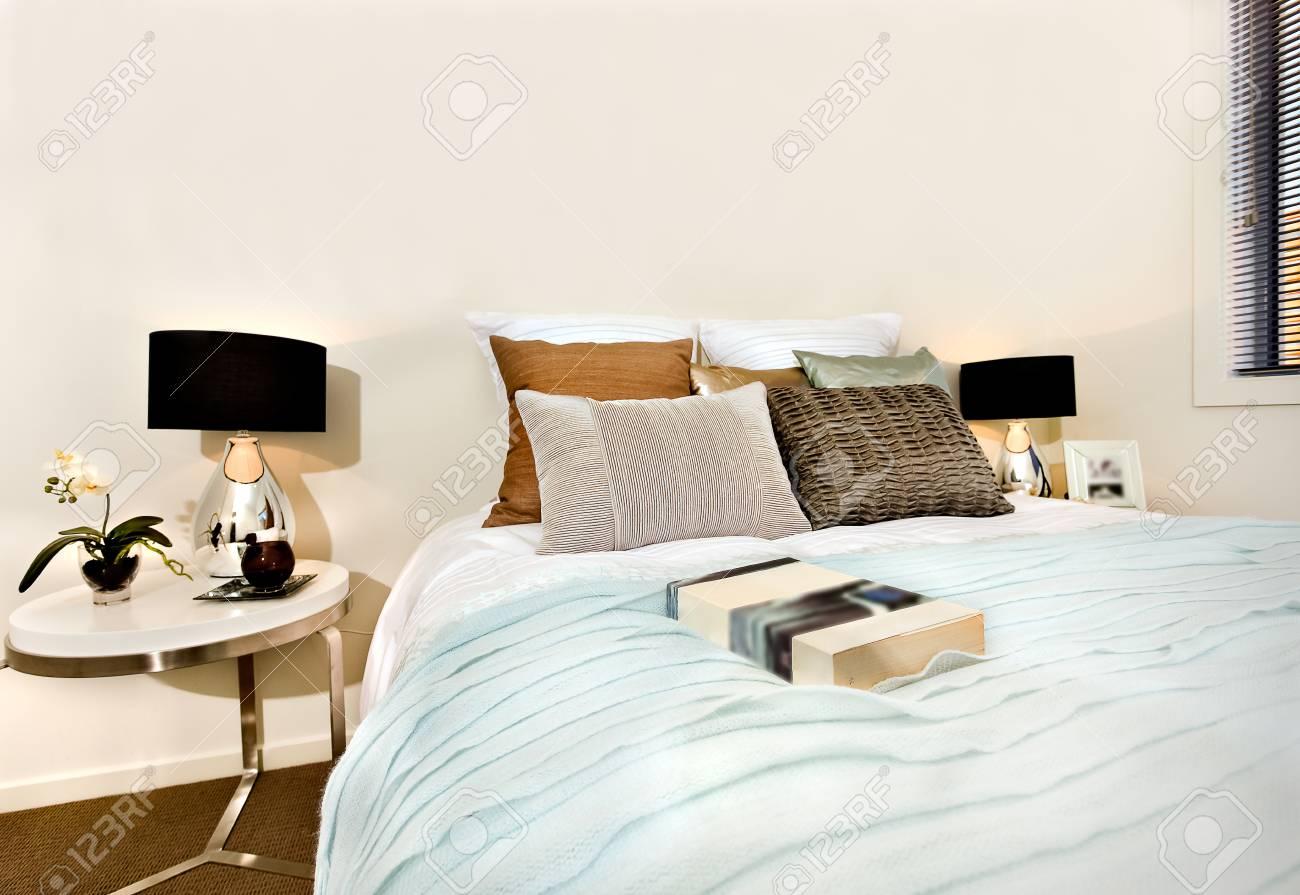 Gros plan d\'une chambre à coucher moderne dans une maison de luxe, il y a  un livre sur le drap de lit bleu clair à proximité des oreillers. Deux ...