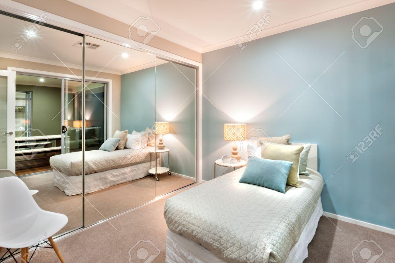Moderno e classico pareti camera da letto sono di colore azzurro, che è  illuminata in luci della lampada da tavolo e una parete è completamente ...