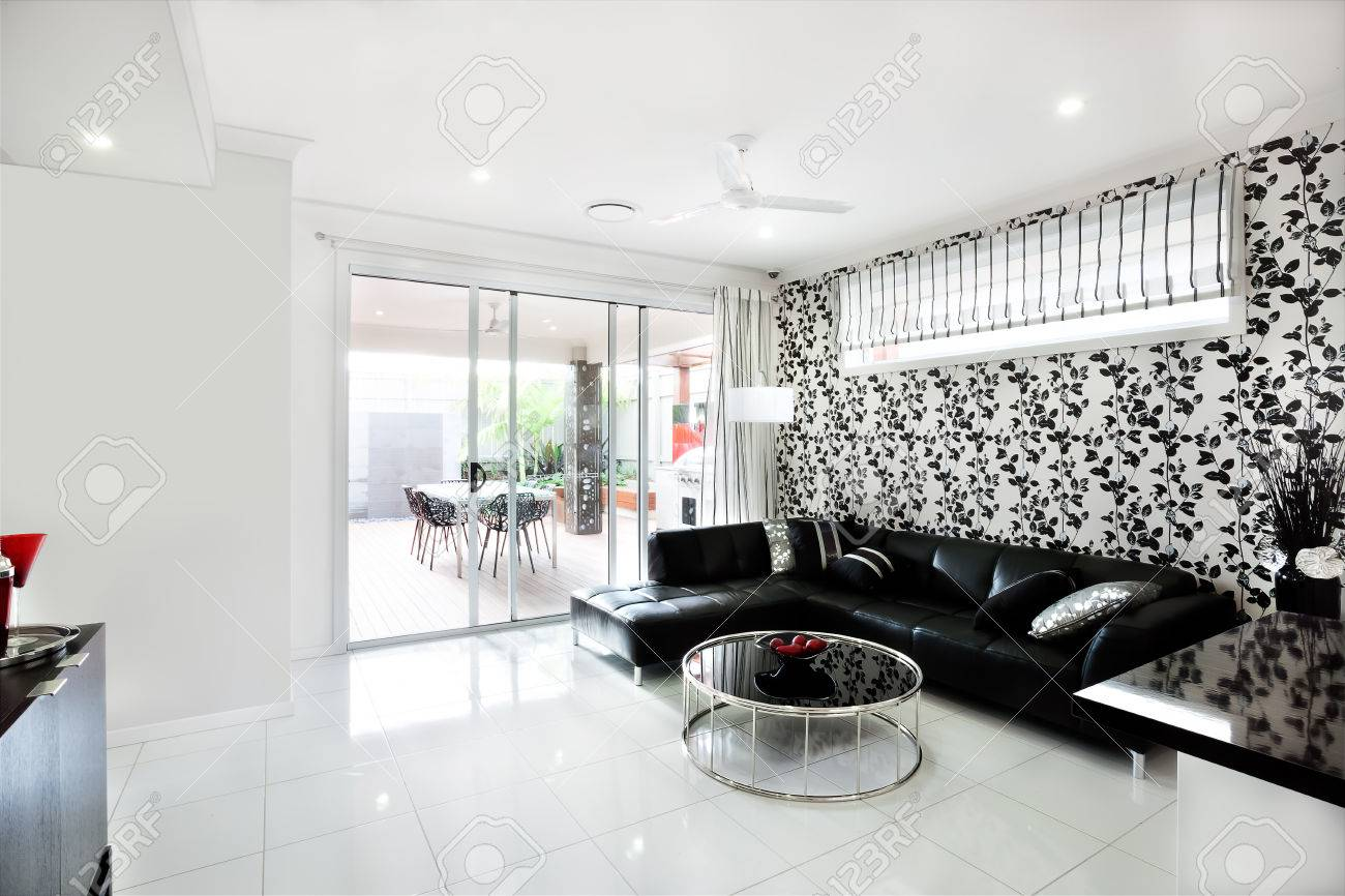 Modern Living Room That Includes A Black Sofa With Pillows And ...