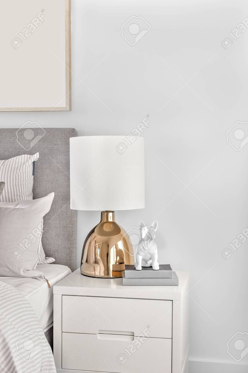 Modern Bedroom With A Gold Color Table Lamp On The Wooden Or