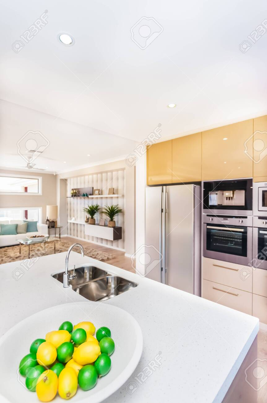 Luxurious kitchen in the house. There are fruits on the plate like lemon near to faucet and the washstand top of the white worktop, The refrigerator and the oven with pantry cupboards mount to the wall. There is well decorated room next to the cuisine - 131212962