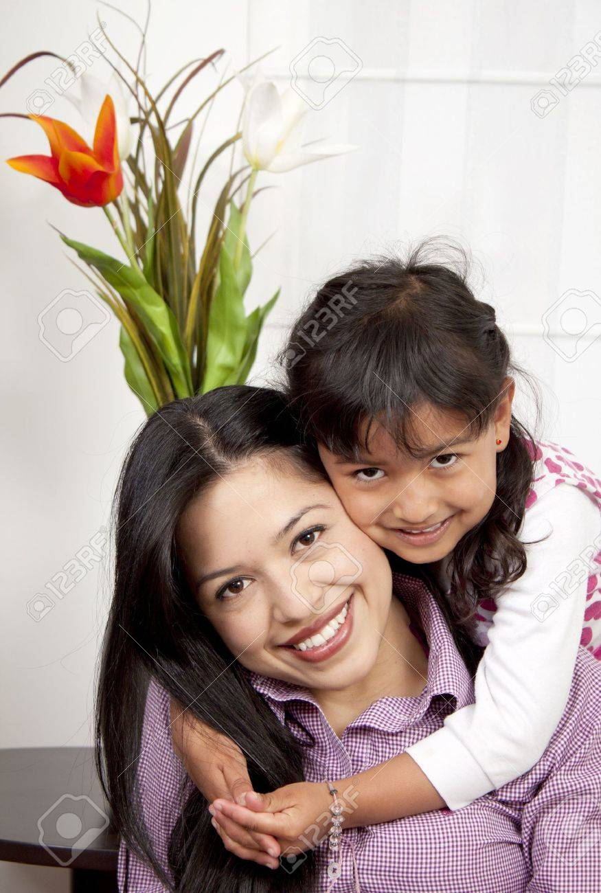Woman and young girl in living room smiling Stock Photo - 13299755
