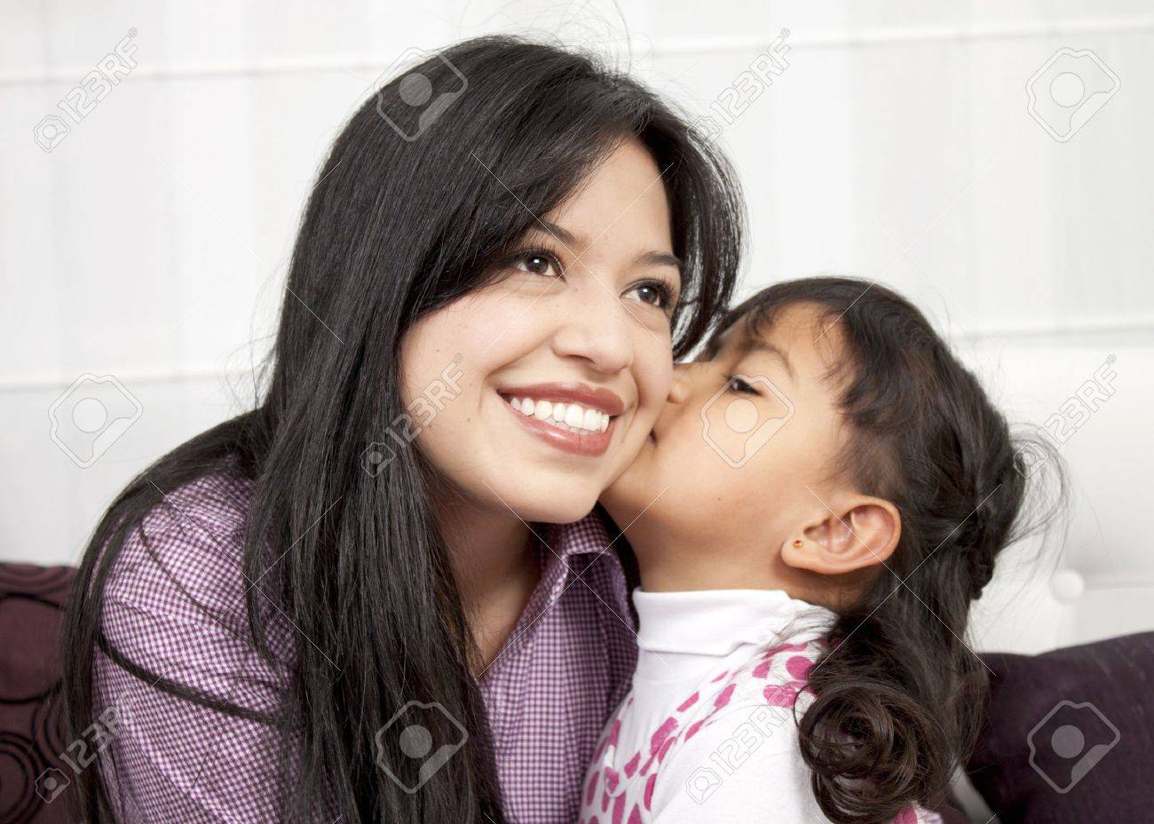 Little girl kissing her mommy in the home Stock Photo - 13299754