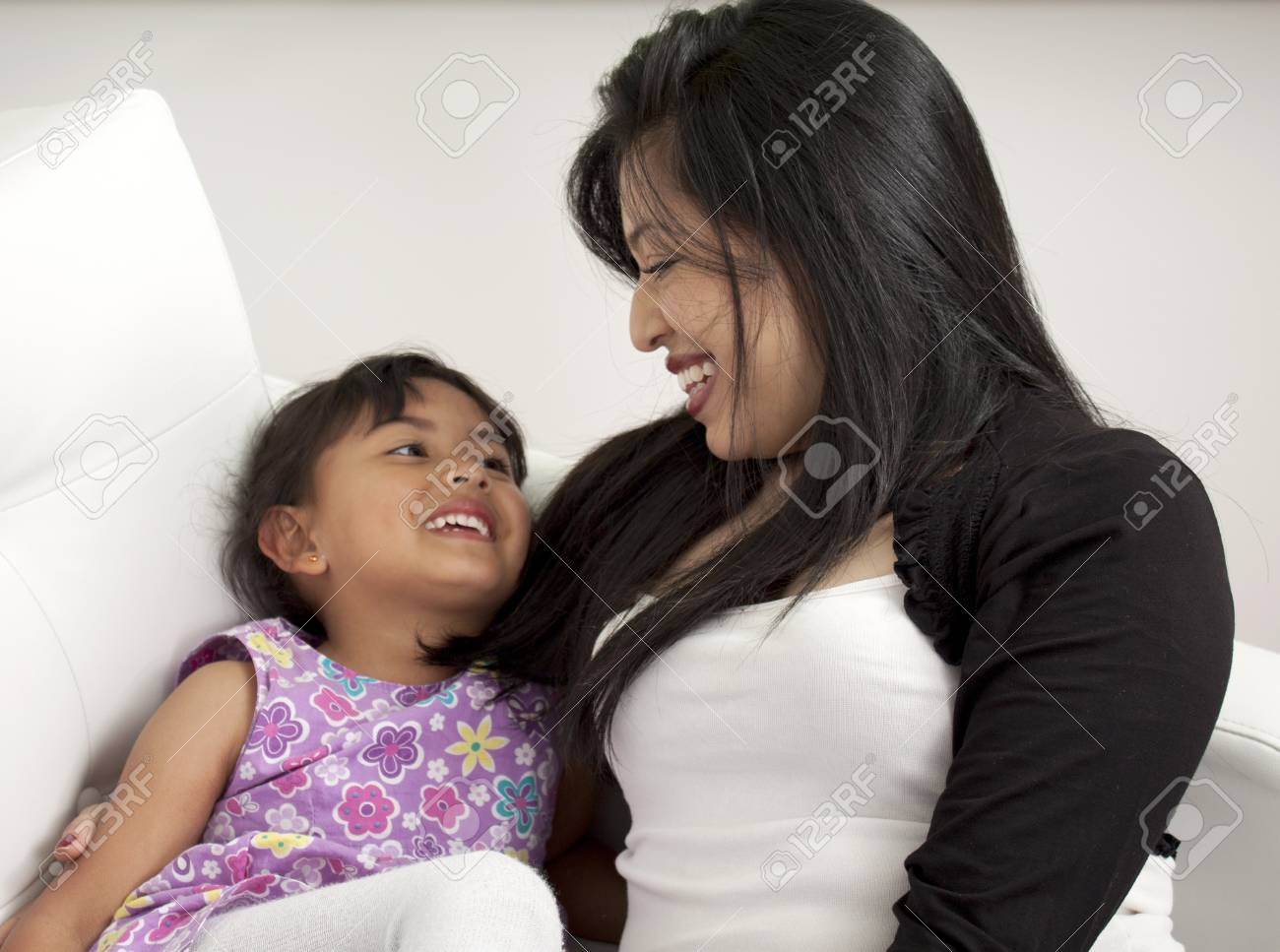 Mother and girl smiling in the living room white Stock Photo - 17382437