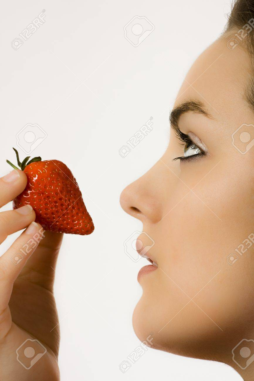 Profile of a beautiful face of a young woman eating a strawberry Stock Photo - 18881553
