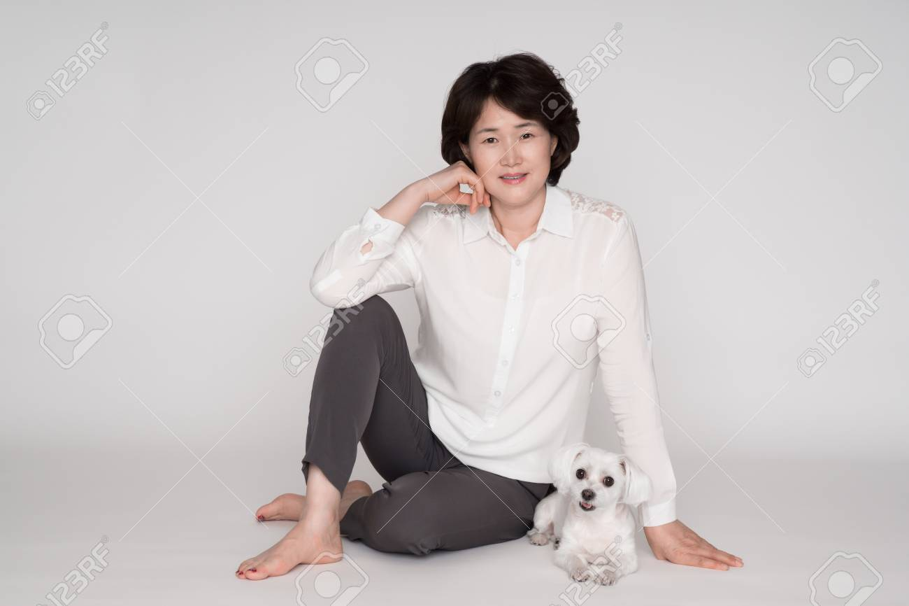 Portrait of beautiful mature woman posing against gray background - 61505475