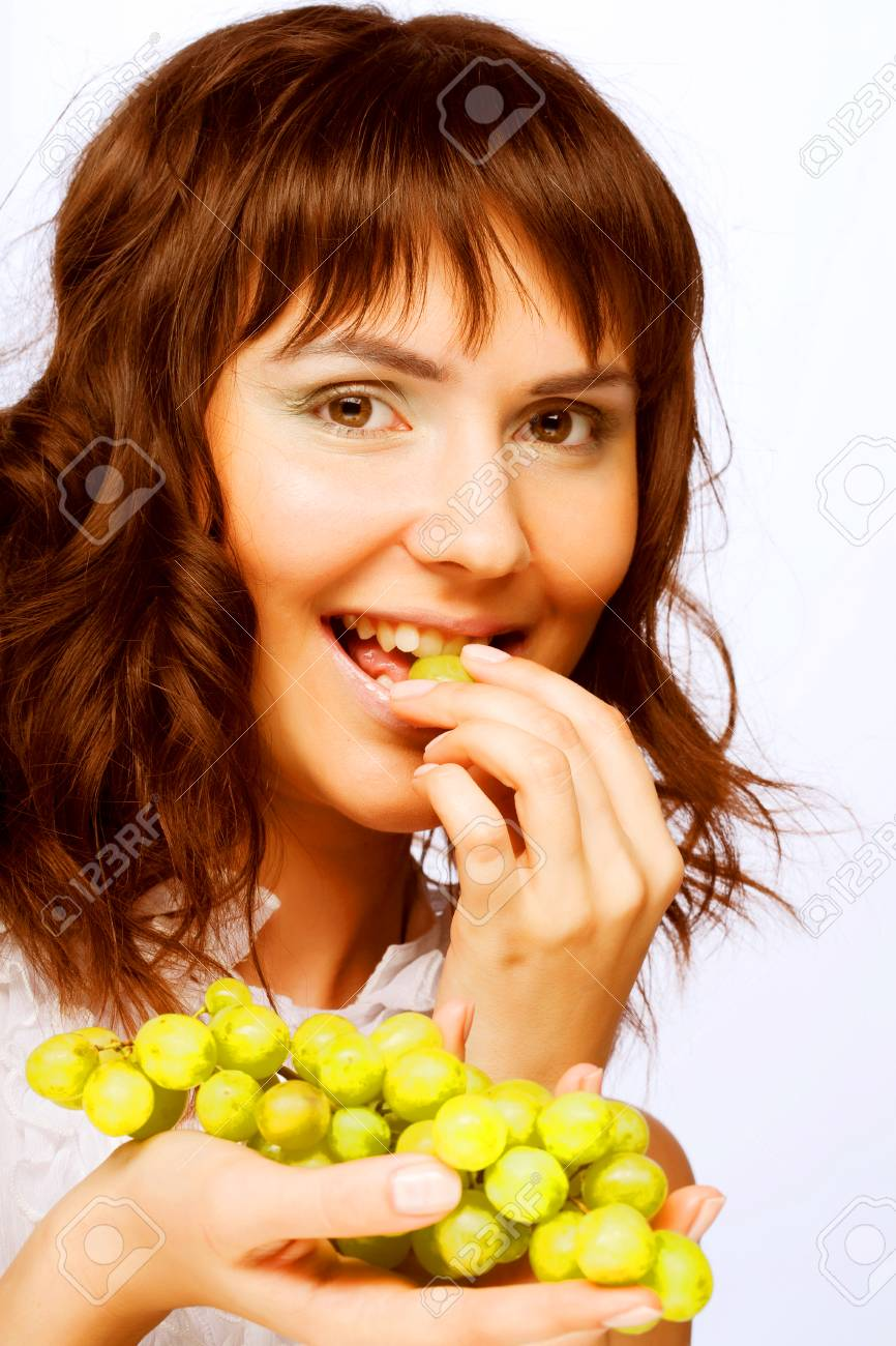 Portrait Of Young Woman With Green Grapes Over White Background