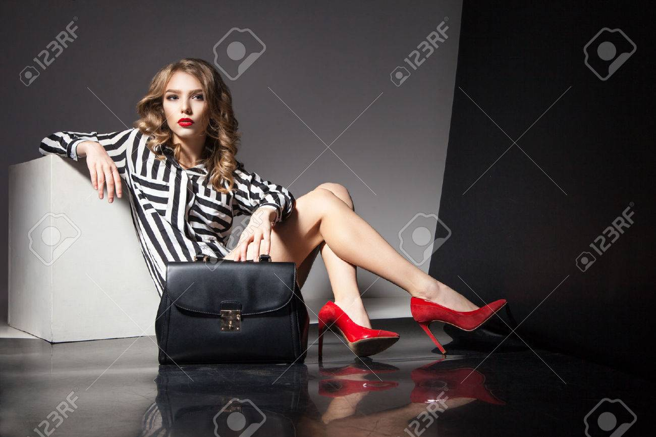 Portrait of elegant beautiful blonde woman with red lips sitting near black fashion bag - 57262642