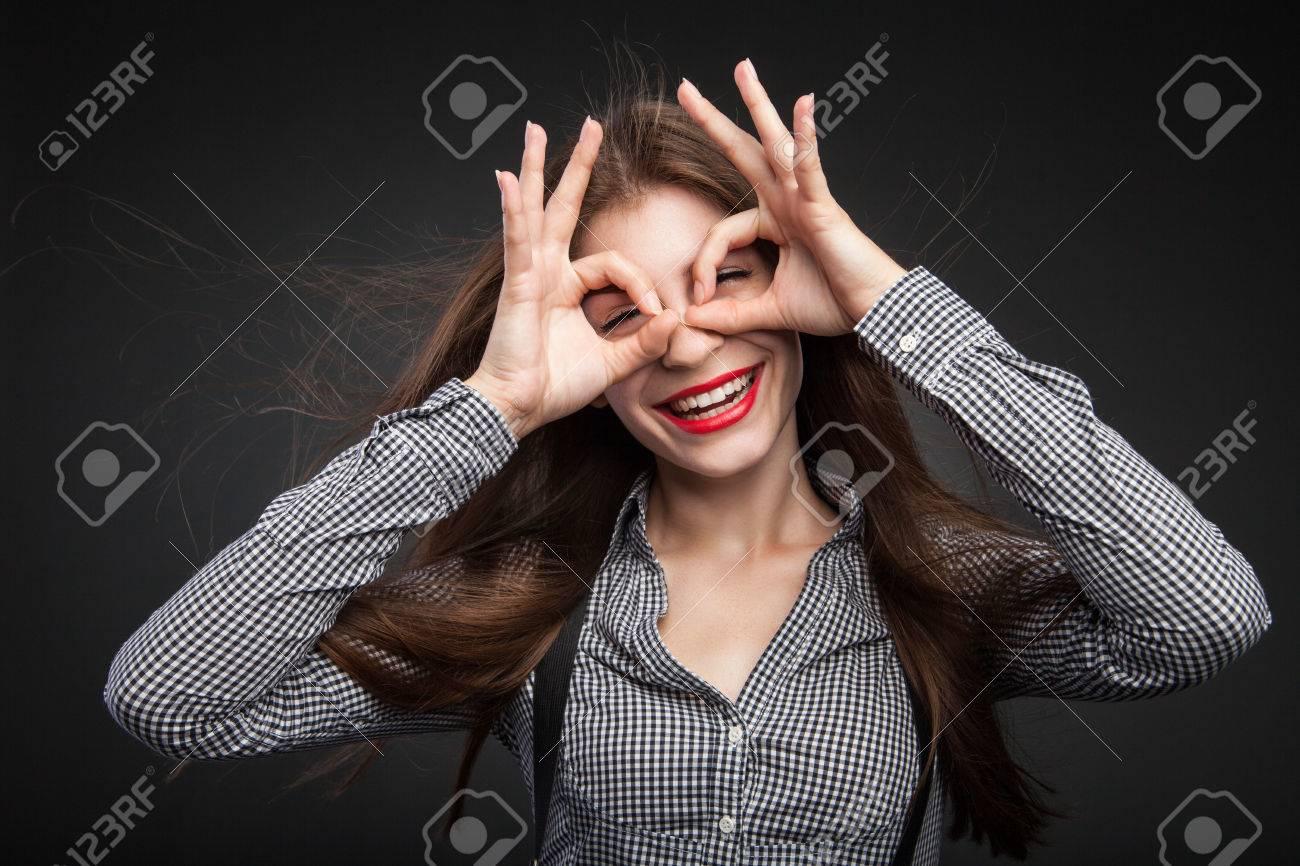 Femme faisant des lunettes de ses mains. bureau look avec chemise à